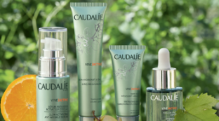 4 Caudaule products shown with an orange, grapes, and leaves representing fresh and clean skin.